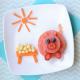 Imagem apresenta prato preparado com frutas, formando um porquinho
