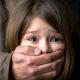 Imagem mostra criança com a boca tapada por adulto